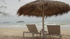 White Sun Loungers Under Palm Leaf Parasol Stock Footage