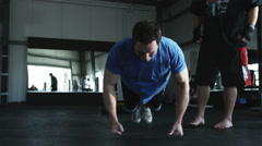 Man doing pushups while his trainer motivates him Stock Footage