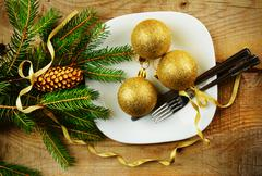 Decorate christmas plate with golden baubles and pines on wooden surface Stock Photos