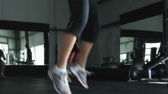 Woman doing jump squats while her trainer motivates her Stock Footage