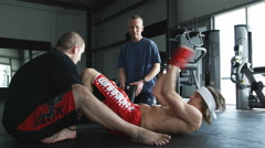 Trainers working with a man to train him for an MMA fight Stock Footage