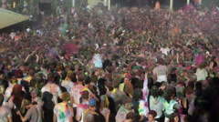 Crowd of people at a Hindu festival throwing colored powder into the air Stock Footage