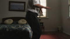 Bored businessman passing the time in a hotel room dancing Stock Footage