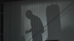 Shadow on the wall of a gym of a man jumping rope Stock Footage
