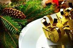 closeup shot decorate christmas plate with golden gifts and pines on wooden s - stock photo