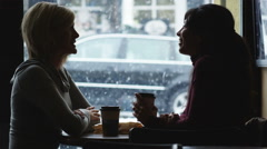 Two women at a coffee shop talking Stock Footage