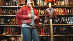 Woman trying on a leather jacket and a cowboy hat at a western store Stock Footage