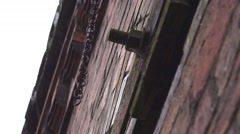 Urban decay rusty old chain swinging from brick wall Stock Footage