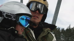 Father and daughter on a chairlift at a ski resort Stock Footage
