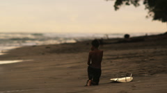 Little boy on the beach with a surfboard Stock Footage