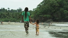 Father and son with dreadlocks walking on the beach Stock Footage