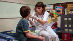 Pediatrician checking sick little patient, child, doctor, home, medical exam - stock footage