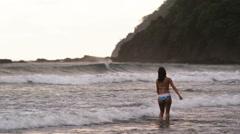 Woman in a bikini walking into the surf Stock Footage