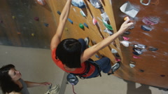 Woman climbing on an indoor climbing wall Stock Footage