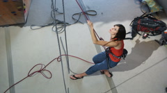 Woman belaying another climber on an indoor climbing wall Stock Footage