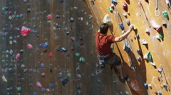 Man climbing on an indoor climbing wall Stock Footage