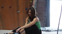 Woman putting on climbing shoes to climb on an indoor climbing wall Stock Footage