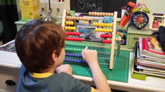 Schoolboy kid doing homework and learning maths counting with abacus at desk Stock Footage