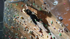 Teenage girl climbing on an indoor climbing wall Stock Footage