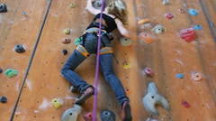 Two young climbers climbing on an indoor climbing wall Stock Footage