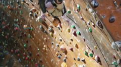 Boy being lowered down from the top of an indoor climbing wall Stock Footage