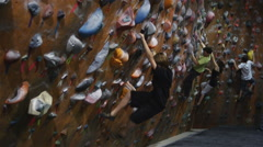 Kids traversing across an indoor climbing wall Stock Footage