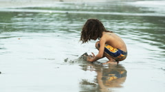 Boy with dreadlocks playing in the sand Stock Footage