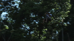Man on a zip line through the trees Stock Footage