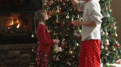 Father and daughter decorating their Christmas tree Stock Footage