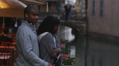 Couple standing by a river with the man trying to keep the woman from feeling Stock Footage