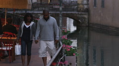 Couple walking by a river holding hands Stock Footage