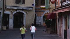 Two women jogging down a European street Stock Footage