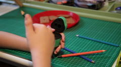 Child pupil at desk after school doing homework with crayons pencils sharpener Stock Footage