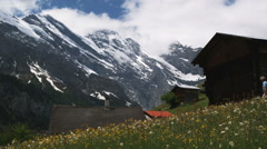 Two hikers hiking through an alpine village Stock Footage