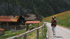 Woman taking photographs on an alpine road Stock Footage