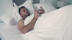 Man lying in bed under white quilt and typing message on cellphone Stock Footage