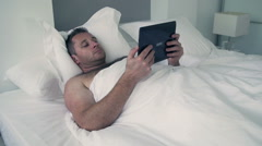 Man lying in bed under white quilt and using tablet Stock Footage