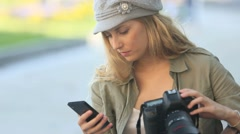Trendy young photographer with camera and smartphone Stock Footage