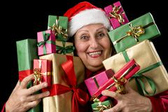delighted old lady hugging a dozen wrapped gifts. - stock photo