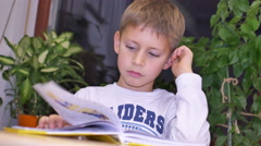 7-year-old cute boy reading a book while sitting at table Stock Footage