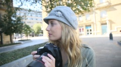 Young woman photographer taking picture in the street Stock Footage