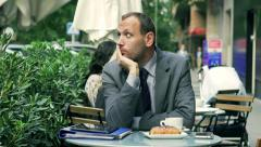 Sad businessman sitting alone in the street cafe Stock Footage