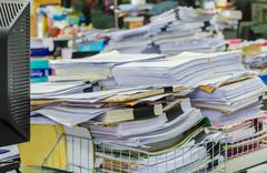Pile of documents on desk stack up high waiting to be managed Stock Photos