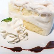 coconut cream cake on a white plate with a bit of whipped cream - stock photo
