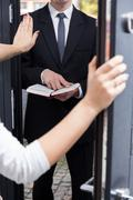 talking jehovah's witness to leave her house - stock photo