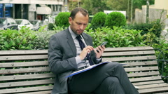 Businessman with cellphone checking documents on the bench Stock Footage