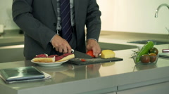 Businessman cutting tomato for his sandwich, steadycam shot Stock Footage
