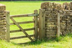 rustic gate in drystone wall in bibury england uk. - stock photo