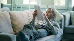 Businessman analyze results and lying on the sofa - stock footage