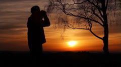 Man is looking with binoculars at sunset Stock Footage